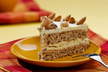 tiffin: cake with almonds and nut on the yellow plate