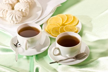 zephyr: white cup of tea with lemon and zephyr, hot drink