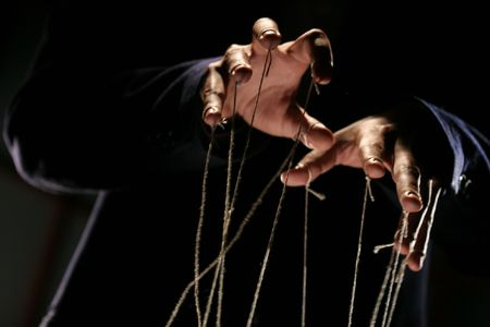 conceptual series: hands of puppeteer with rope