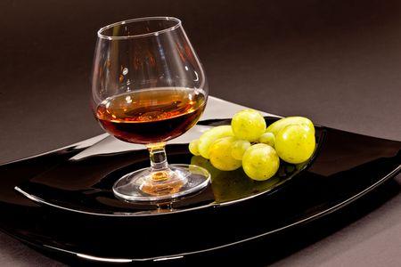 коньяк: drink series: glass of cognac grapes on the black plate Фото со стока