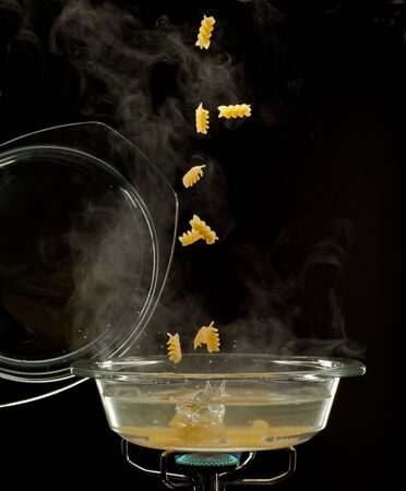 boiling water: pasta is falling into a boiled water Stock Photo