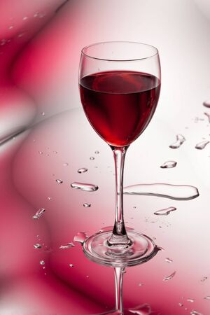 glass of red wine on abstract colorful background photo
