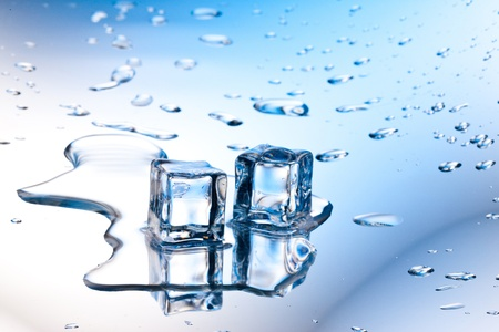 melting: ice cube with pure water on reflective surface