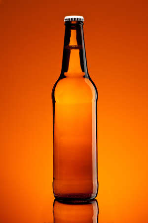 brown bottle with beer over brown background Stock Photo - 12917914
