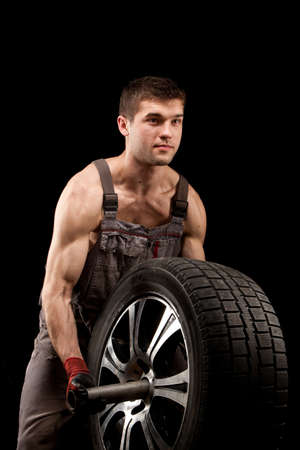 repairman with big wheel over black background Stock Photo - 13214479