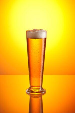 foamy: glass of foamy beer over golden background
