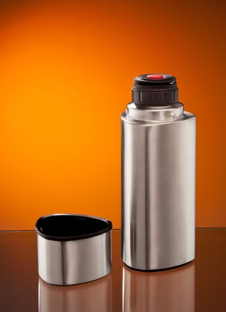 modern steel vacuum flask over orange background photo