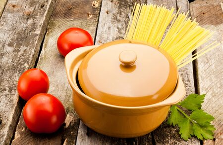 parsel: ceramic pan with pasta on old wooden plank