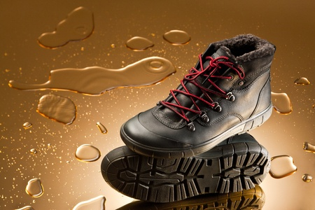 black winter shoes over golden background with water drops photo