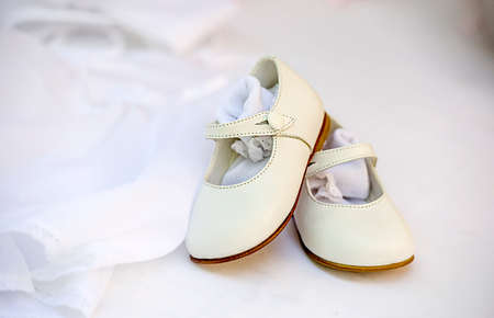 Small baby girl shoes on lace dress as background