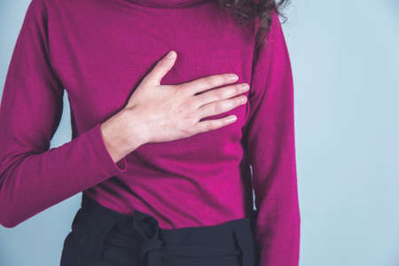 woman hand in ache heart on gray background