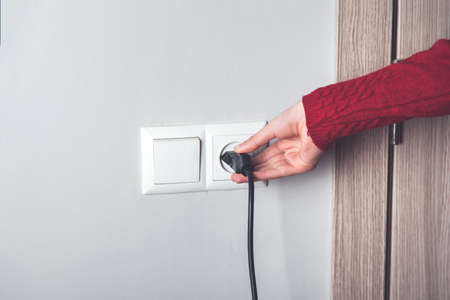 A woman hand pulls a black cord in home Stock Photo