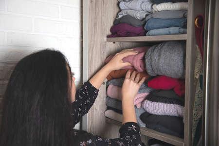 woman  arranges clothes in the closet