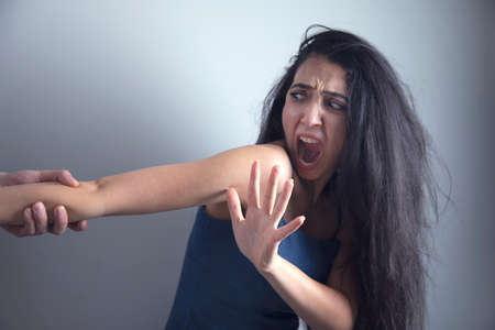 man beat sad woman on grey background Banque d'images