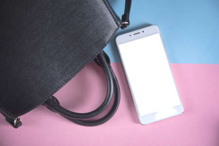 smart phone and  bag on the color table 스톡 콘텐츠