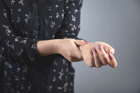 young woman hand pulse on grey background