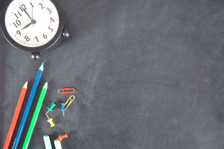 different stationery and clock on the black table