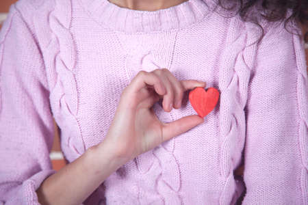 young woman hand holding red wooden heart
