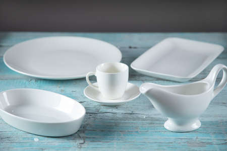 different white dishes on the blue wooden table