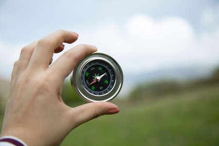 woman hand holding compass in nature background