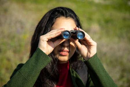 woman looks through the binoculars in mountain background