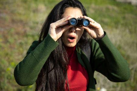 surprised woman hand binoculars on nature background
