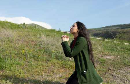 young prayer woman in the nature background