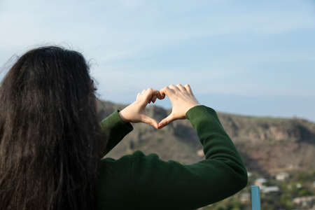 young woman hand heart in the nature 版權商用圖片