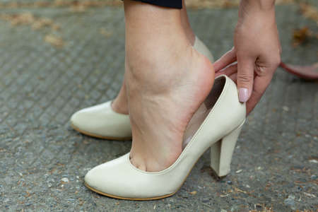 woman hand in ache foot in high shoes in street