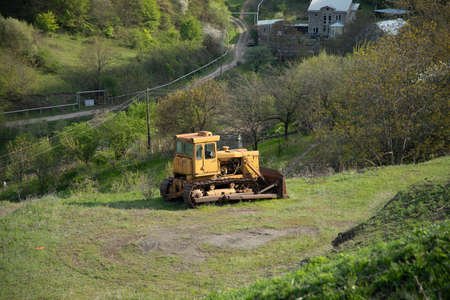 yellow chain tractor in green grass nature background