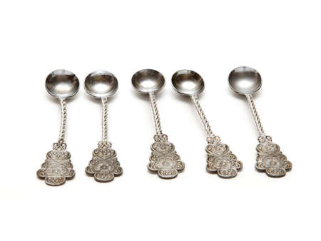 five silver spoons on a white background