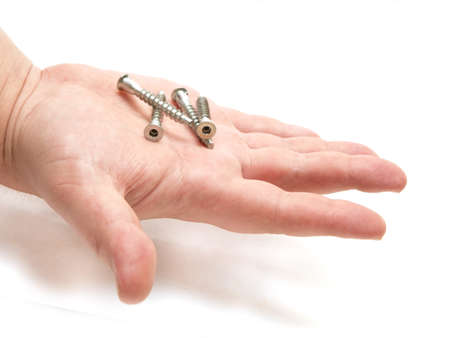 four bolts on a human hand on a white background