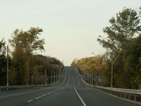 the asphalted road leaving in a distance Stock Photo