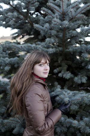 beautiful girl with dark hair, wearing a brown coat against the green pine