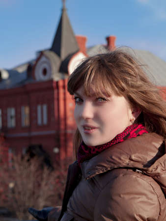 beautiful girl with dark hair, wearing a brown coat in the red building