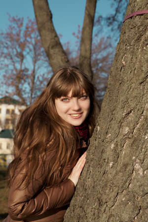 beautiful young girl with dark hair and brown coat standing near a tree