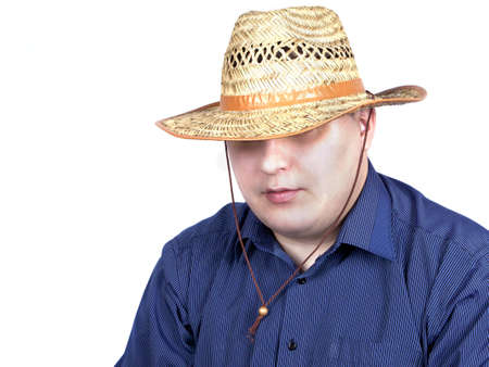 young man in a blue shirt with a straw hat in hand on a white background photo