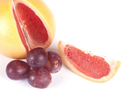 Fruit composition of ripe grapefruit and grapes on a white background
