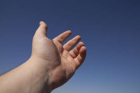 left human hand against the blue sky