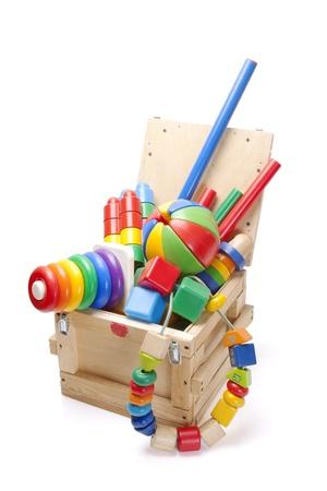 juguetes de madera: caja de madera con muchos juguetes sobre fondo blanco Foto de archivo