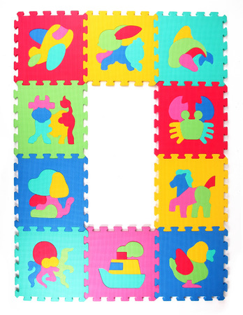 Multicolored frame of foam puzzle a white background photo