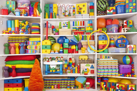 baby blocks: Shelf with many colored toys Stock Photo