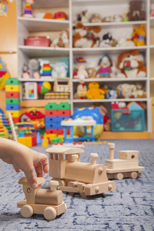 play room: wooden train in the play room and many toys Stock Photo