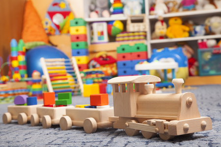 wooden train in the play room and many toys Stock Photo