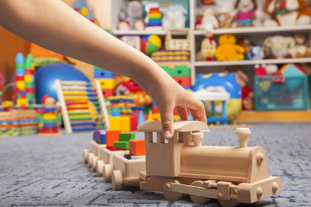 wooden train in the play room and many toys Imagens