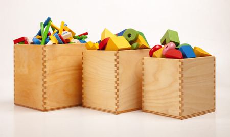 Three wooden boxes with very many toys Stockfoto