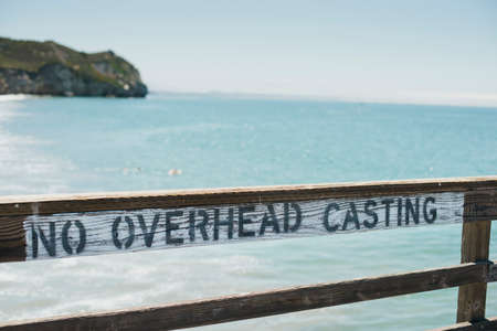 Sign on the pier that reads no overhead casting Stock Photo