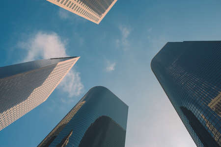A group of four sky scrapers seen reaching to the blue sky Stock Photo