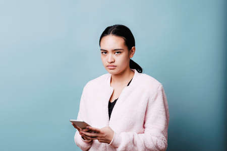 Frustrated teen reacts to content on her cell phone Stock Photo