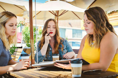 Three young millennial females have a business meeting at an open air cafe